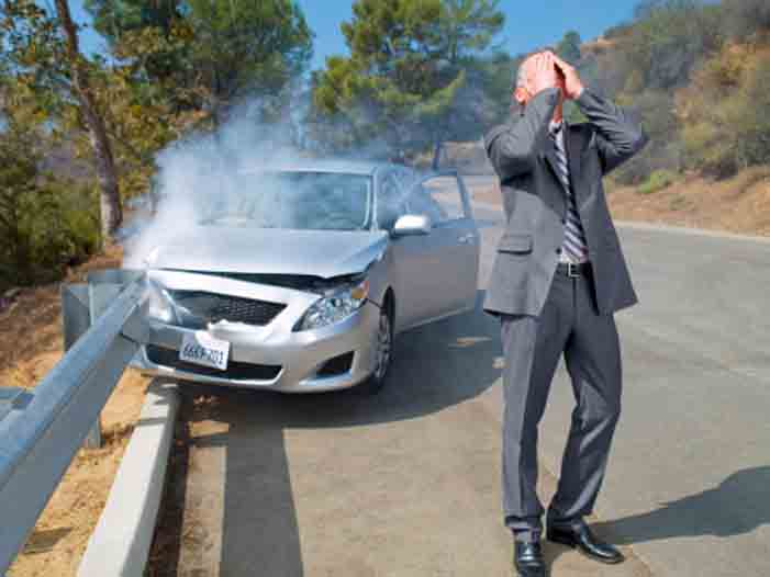Frustrated businessman standing next to car wrecked on guardrail
